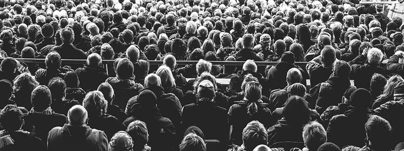 Black and white image of crowd watching a stage