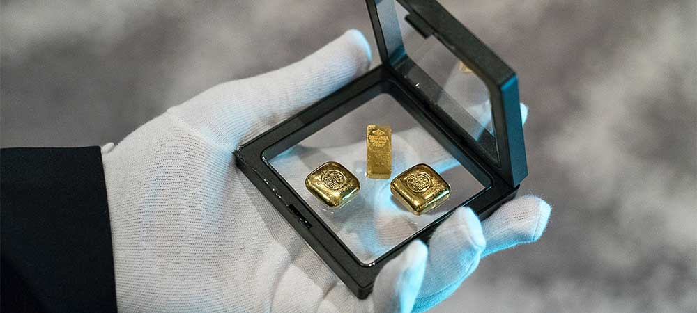 Glove holding three Gold bullion investment bars in a case