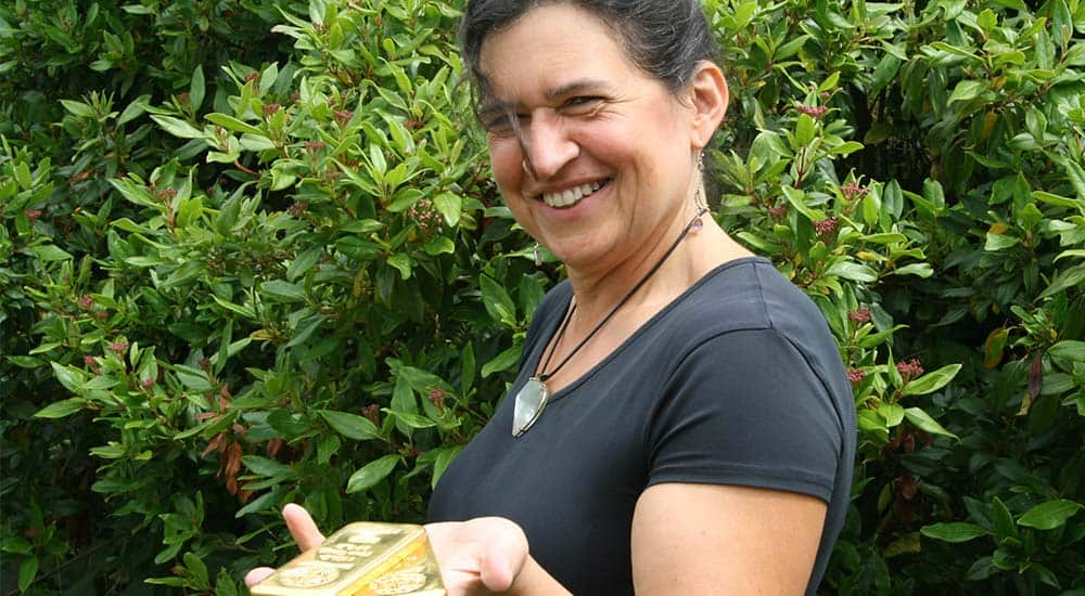 Caroline Savage, Managing Director of Bleyer Bullion, holding gold bullion investment bars