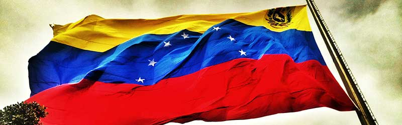 A Venezuela flag blowing in the wind against a stormy sky
