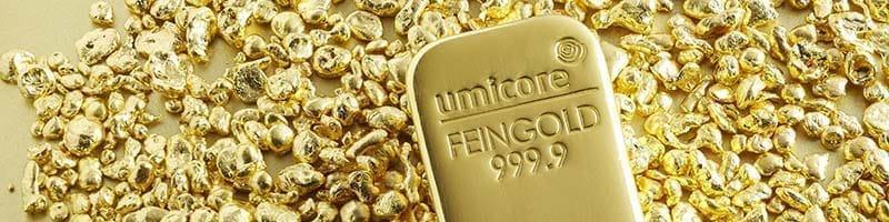 Umicore gold bullion bar lying amongst gold flakes
