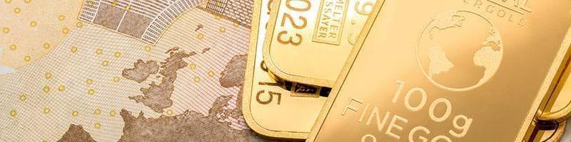 Gold bullion bars lying on a Euro note