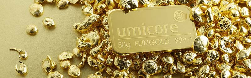 50g gold Umicore bullion bar lying on a bed of gold
