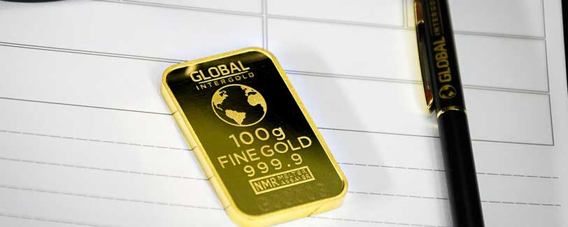 Gold bullion investment bar lying next to a pen