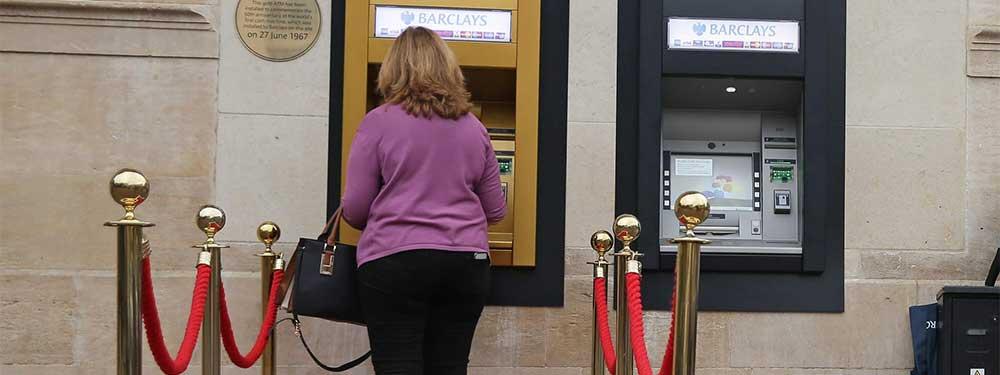 Red carpet leading to a solid gold cash point with someone withdrawing money