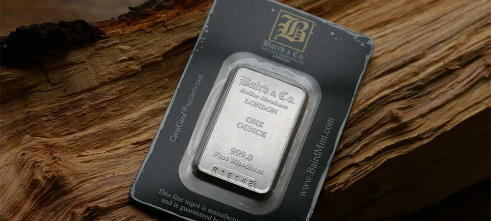 1oz Baird's Rhodium Investment Bullion Bar lying on wood, now available from Bleyer