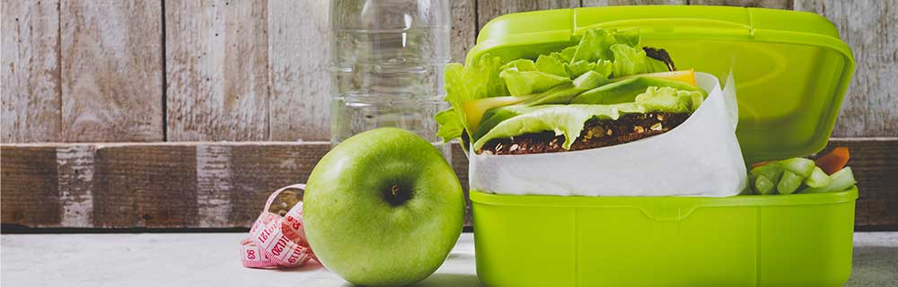 Green lunchbox with sandwich and green apple